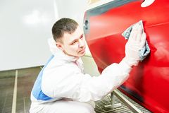 Auto mechanic wiping car. Auto mechanic worker wiping car body at automobile repair and renew service station shop in painting chumber Stock Photos