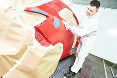 Auto mechanic wiping car. Auto mechanic worker wiping car body at automobile repair and renew service station shop in painting chumber Stock Photography