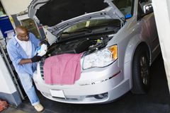 Auto Mechanic At Work. An African American male mechanic refilling fluid in car's engine at garage Royalty Free Stock Photo