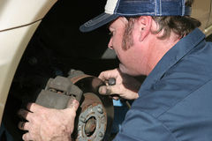 Auto Mechanic At Work. An auto mechanic working on brakes Stock Image