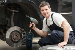 Auto mechanic at work. Cheerful auto mechanic sitting near the car and holding a work tool stock photography