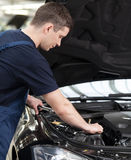 Auto mechanic at work. Confident auto mechanic working on car engine royalty free stock photography