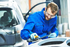 Auto mechanic worker  polishing bumper car Stock Images