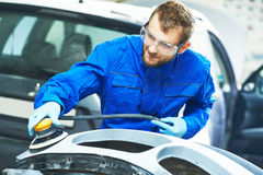 Auto mechanic worker polishing bumper car Stock Image