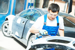 Auto mechanic worker  polishing bumper car Royalty Free Stock Image