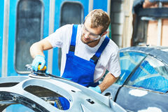 Auto mechanic worker polishing bumper car Stock Images