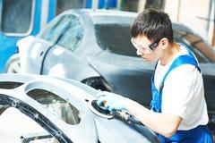 Auto mechanic worker polishing bumper car Royalty Free Stock Photos