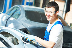 Auto mechanic worker polishing bumper car Royalty Free Stock Photos