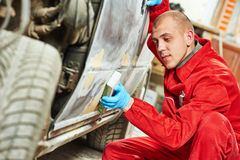 Auto mechanic worker sanding body car Stock Photo