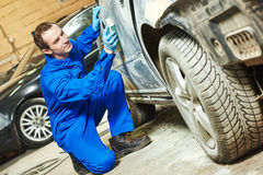 Auto mechanic worker sanding bumper car Royalty Free Stock Photography