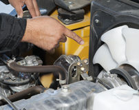 Auto mechanic working on a car in garage. Engine repair. The worker shows on a detail Stock Photography