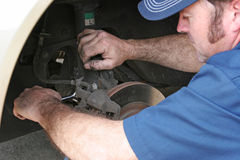 Auto Mechanic Works on Brakes. Auto mechanic working on a car's front disc brakes Stock Image