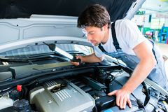 Auto mechanic working in car service workshop. Auto mechanic working on car in service workshop stock images