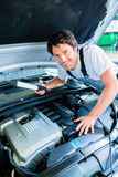 Auto mechanic working in car service Stock Images