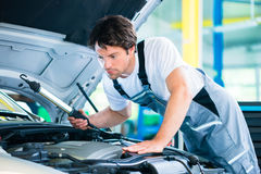 Auto mechanic working in car service workshop Royalty Free Stock Image