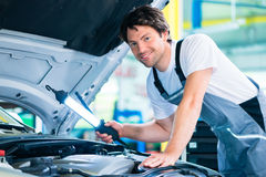 Auto mechanic working in car service workshop. Working Stock Photo