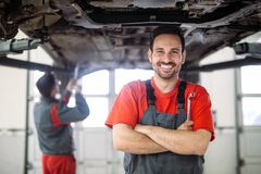 Auto mechanic working in garage. Repair service. Young auto mechanic working in garage. Repair service stock images