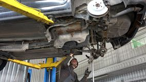 Auto mechanic working with hammer under automobile. In car repair service shop stock footage