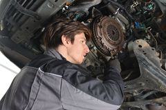 Auto mechanic working under the car and changing clutch Royalty Free Stock Image