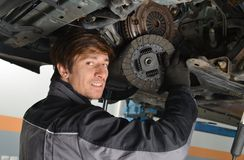Auto mechanic working under the car and changing clutch Stock Photo