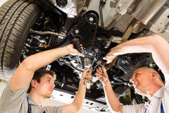 Auto mechanic working under car Stock Images