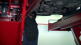 Auto mechanic working under the car stock footage