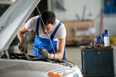 Auto mechanic working under the hood Royalty Free Stock Image