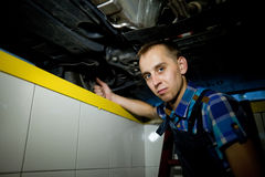 Auto mechanic working underneath a lifted car. Auto mechanic working in garage stock photos