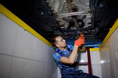 Auto mechanic working underneath a lifted car. Auto mechanic working in garage stock photography