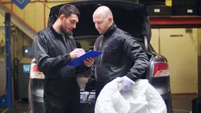 Auto mechanics with car tire at workshop. Car service, repair, maintenance and people concept - two auto mechanics with tire and clipboard talking at workshop stock video