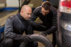 Auto mechanics changing car tires at workshop. Car service, repair, maintenance and people concept - two auto mechanics changing car tires at workshop Stock Image