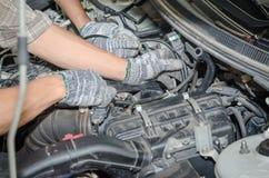 Auto mechanics repairing a car LPG system. Royalty Free Stock Photos