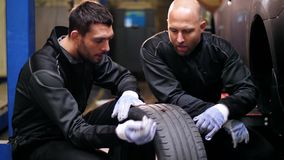 Auto mechanics repairing car tire with blowout. Car service, repair, maintenance and people concept - two auto mechanics repairing wheel tire at workshop stock video