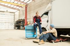 Auto Mechanics Talking At Work. Young bearded male car technician chatting with his colleague while resting near broken truck in large service garage Royalty Free Stock Photo