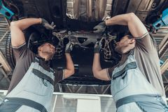 Auto Mechanics Working Underneath Lifted Car stock photography