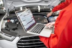 Auto mechanicy robi diagnostykom z laptopem obraz stock