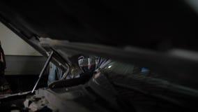 Auto mechanik podnosi w górę samochodowego, używać electro hydraulicznego dźwignięcie w usługa podczas dołączonej inspekci zbiory wideo
