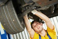 Auto mechanik przy samochodową zawieszenia naprawy pracą obraz stock