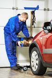 Auto mechanik przy samochodowym reflektoru checkup zdjęcie stock