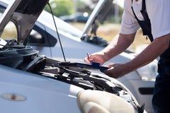Auto mechanik sprawdza samochodowego silnika i pisze na schowku Obraz Royalty Free
