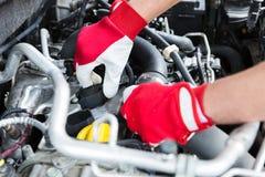 Auto mechanik sprawdza samochodowego silnika iskrową prymkę depeszuje fotografia royalty free