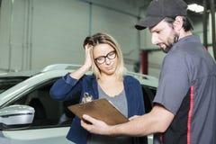 Auto mechanika i kobiety klient w garażu obraz stock