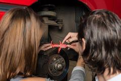 Auto mechanika i kobiety praktykant zmienia samochód zdjęcia stock