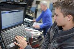 Auto mechanika praktykanta i nauczyciela spełniania testy przy mechanik szkołą obraz stock