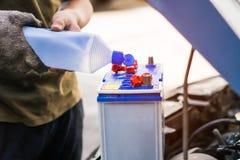 Auto mechanika uses sprawdzać i utrzymanie samochodowa bateria Zdjęcia Stock