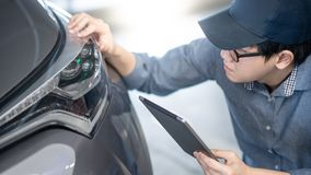 Auto mechanische het controleren autokoplamp die tablet gebruiken stock foto's