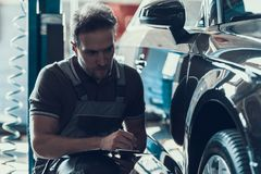 Auto mekaniker Holding Clipboard av tjänste- beställning arkivbild