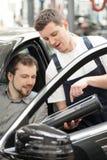 Auto mekaniker och bilägare. royaltyfri foto