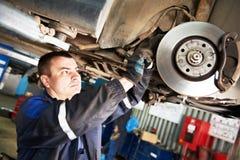 Auto mekaniker på bilbromsbackar som eximining Arkivfoton