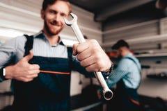 Auto mekaniker Posing With Wrench Tjänste- station arkivfoto